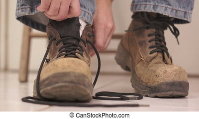 Male Putting On Old Workboot - Low angle shot of an...
