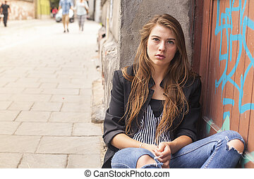 Young hipster girl sitting on the street