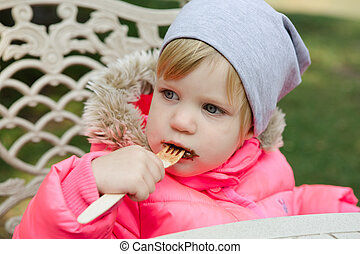 Child eating waffles with chocolate in park