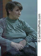 Melancholic woman - Vertical view of older melancholic woman...