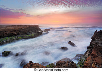 Stunning sunrise and ocean flows over tidal rocks
