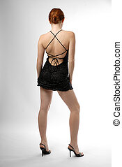Model in short dress with nude back - Young woman stands in...