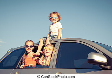 Happy brother and his two sisters are sitting in the car at...
