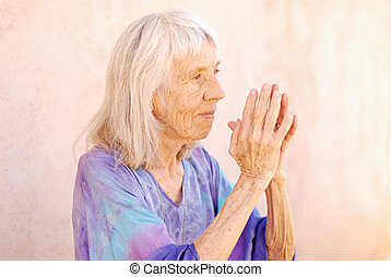 Senior Woman Namaste - New Age senior woman holding her...