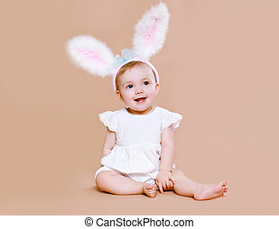 Charming baby sitting in costume easter bunny