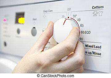 Woman Selecting Cooler Temperature On Washing Machine To...