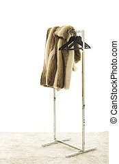 Fur Coat Draped Over Clothing Rack with Hangers in Studio...