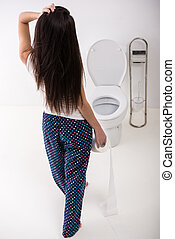 Woman in toilet - Back view of woman with paper in toilet in...