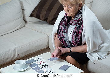Senior woman playing cards alone - Senior woman sitting on...