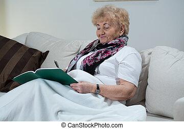 Woman doing crossword puzzle - Portrait of senior woman...