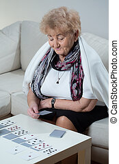 Elder woman playing solitaire - Active elder woman playing...