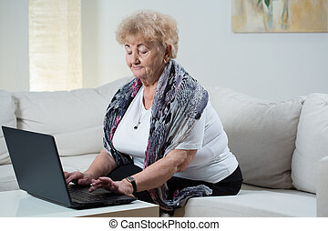 Modern senior woman typing on the keyboard