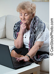 Elderly woman using laptop - Elderly woman sitting on sofa...