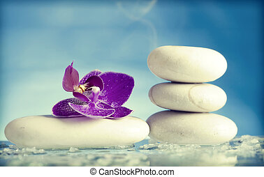 Spa still life with pink orchid and white zen stone in a...