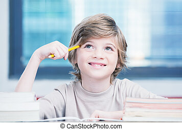 Happy elementary schoolboy thinking about ideas for...
