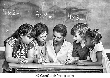 Attractive young female teacher checking multi race...