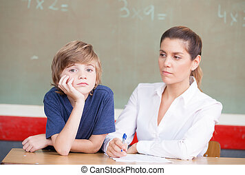 Stressed and Unhappy Schoolboy Studying In Classroom With Teache