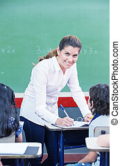 Happy female teacher checking students work at primary...