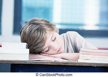 Tired child sleeping while studying in the primary school classr