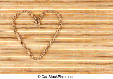 Symbolic heart made of rope lying on a bamboo mat, as...