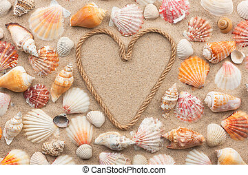 Symbolic heart made from rope and seashells lying on the...