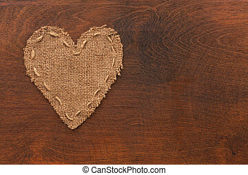 The symbolic heart of burlap lies on a wooden surface, as a...