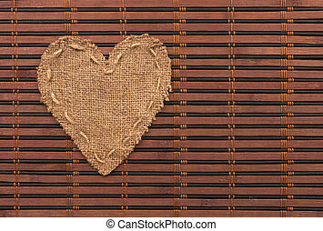 The symbolic heart of burlap lies on a bamboo mat, as a...