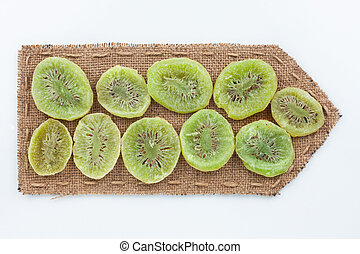 Pointer of burlap with dried kiwi, on a white background