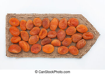 Pointer of burlap with dried apricots , on a white...