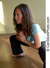 Yoga Squat - Middle aged female in a yoga pose: a deep squat...