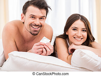 Sex - Young attractive couple in bed with a condom.