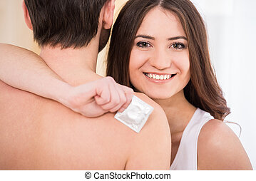 Sex - Young couple in the arms. Woman is holding a condom.
