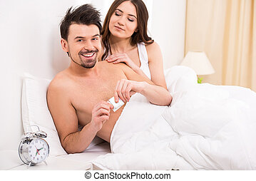 Sex - Young man is opening condom with woman in bed.