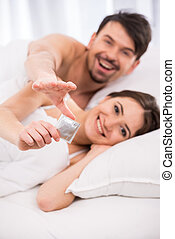 Sex - Smiling young couple in bed with condom are looking at...