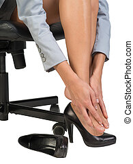 Businesswoman sitting on chair and massaging her feet -...