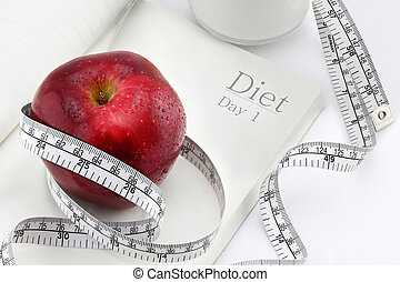 Red apple on a notebook and measuring tape, Diet concept