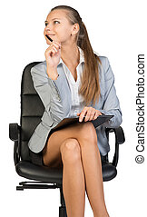 Businesswoman sitting on office chair with clipboard and pen...