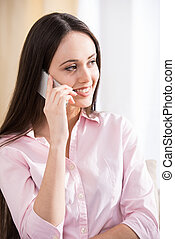 Woman with phone - Young woman is using cellphone while...