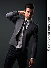Attractive young male fashion model in suit jacket and tie -...