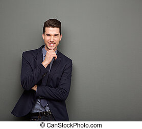 Smiling young business man standing with hand to chin -...
