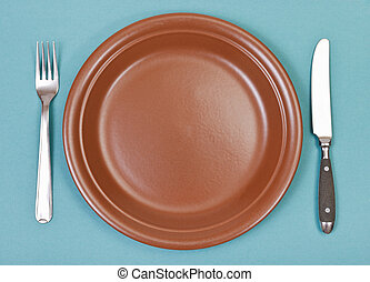 top view of ceramic plate, fork, knife on green - top view...