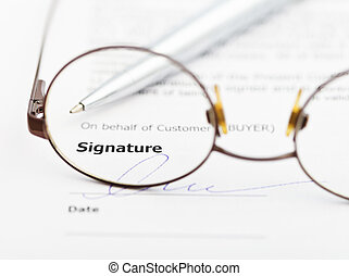 signature of agreement and pen through eyeglasses -...
