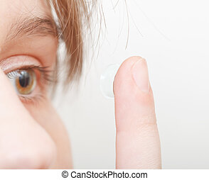 woman inserts contact lens in eye - young woman inserts...