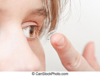 young woman inserts corrective lens in eye close up