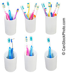 collection of toothbrushes in ceramic glases isolated on...
