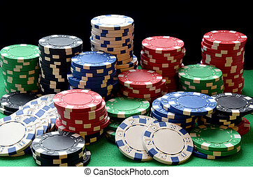 Red, blue, green, white and black poker chips pile on green...