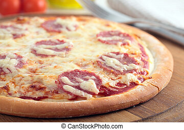 Pizza with salami and cheese on a wooden board