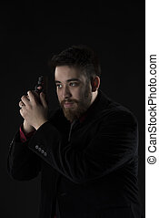 Goatee Man in Black Suit Holding Weapon - Half Body Shot of...
