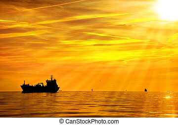 Ship - Cargo ship on sea in the rays of the setting sun