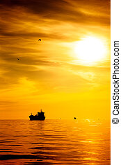 Ship - Cargo ship on sea in the rays of the setting sun.